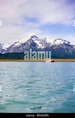 A motorboat motor cruising yacht anchored in a beautiful wilderness bay cove near snow-capped mountains, Glacier Bay National Park, Alaska, USA - Stock Photo
