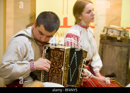 Reconstruction of an ethnic old  wedding.The man in the embroidery plays the harmonica - Stock Photo