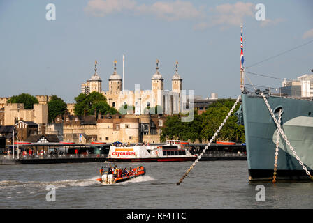 The Tower of London seen across the river Thames, with the bow of HMS Belfast moored in the foreground. - Stock Photo
