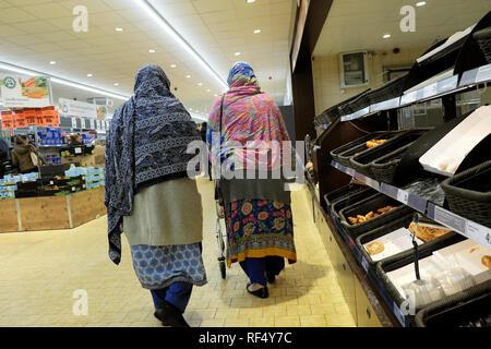 Lidl supermarket shoppers two elderly old women wearing headscarf headscarves shopping together walking past empty bakery shelves in UK  KATHY DEWITT - Stock Photo