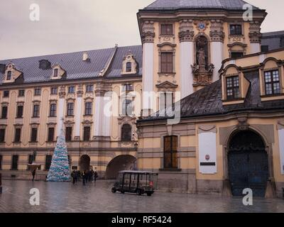 University of Wroclaw Architecture with a Christmas Tree and Light Snow and a Group of Tourist with a Guide - Stock Photo