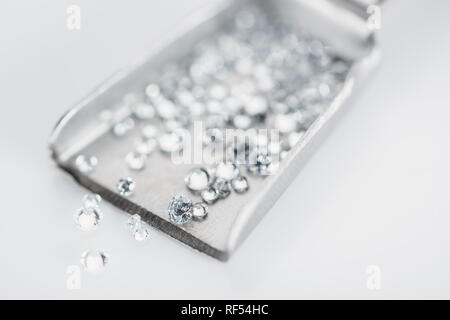 selective focus of small diamonds on spatula isolated on grey - Stock Photo