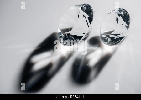 shiny clear diamonds with shadows on grey background - Stock Photo