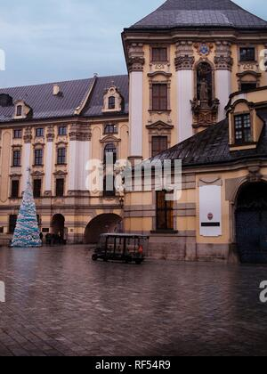 Baroque Architecture and Christmas Tree and Light Snow and a Group of Tourist with a Guide - Stock Photo