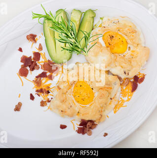Cloud eggs and avocado with cheese and herbs  on a white plate - Stock Photo