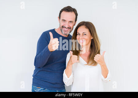 Beautiful middle age couple in love over isolated background success sign doing positive gesture with hand, thumbs up smiling and happy. Looking at th - Stock Photo