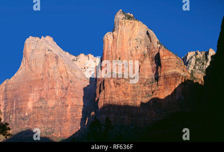 USA, Utah, Zion National Park, Morning light on Mount Abraham (left) and Mount Isaac (right) in the Court of the Patriarchs; Zion Canyon. - Stock Photo