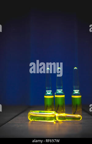 yellow narcotic drugs, chemicals, vitamins in ampoules on a blue background. artistic dark filter. low key photo. - Stock Photo
