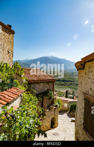 Southern France on a sunny day: A dreamy street in the village Eus near the spanish border with the french Pyrénées in the distance. - Stock Photo