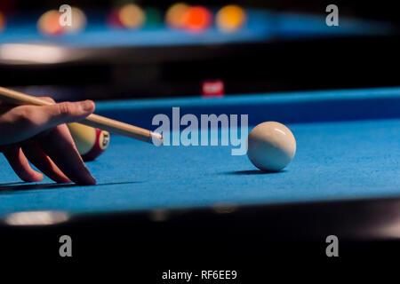 Playing billiard. Billiards balls and cue on blue billiards table - Stock Photo
