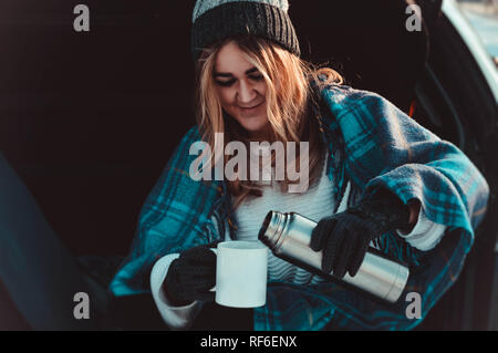 Young woman sitting on car trunk with coffee cups and thermos in winter field