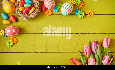 Colorful Easter still life with eggs and fresh spring flowers arranged in opposite corners on green wooden boards with center copy space - Stock Photo