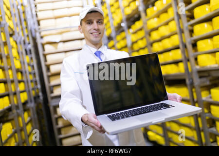Worker shows an empty screen laptop in stock cheese - Stock Photo