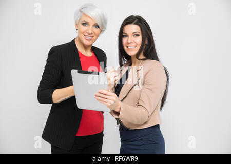 Portrait of two young girls with a tablet in their hands isolated on a light background - Stock Photo