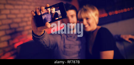 Couple taking selfie on mobile phone in bar - Stock Photo