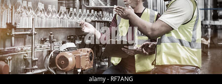 Two factory workers discussing while monitoring drinks production line - Stock Photo