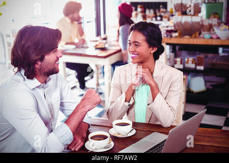 Smiling man and woman using a laptop while having cup of coffee - Stock Photo