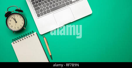 Time management concept. Computer laptop and alarm clock on green color office desk, top view, copy space - Stock Photo