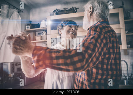 Senior couple dancing together in kitchen - Stock Photo