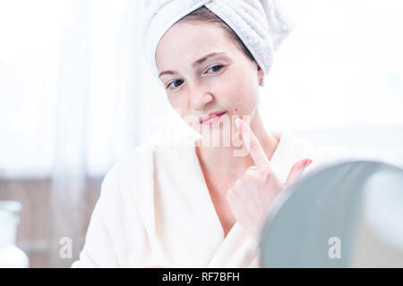 Beautiful unhappy young woman with a towel on her head detects acne on her face. Concept of hygiene and care for the skin - Stock Photo