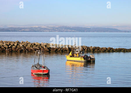 Two small boats anchored at high tide off the seafront at Morecambe with the famous view across Morecambe Bay towards the Lake District. - Stock Photo