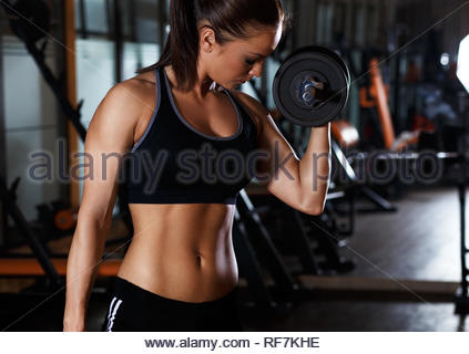 Young woman exercising with dumbbells weight in the gym. - Stock Photo