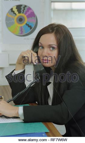 Young businesswoman sitting behind desk and talking on telephone in office setting - Stock Photo