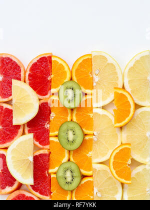 Creative pattern of sliced fruits - kiwi, orange and grapefruits, flat lay style with a copy space on top - Stock Photo