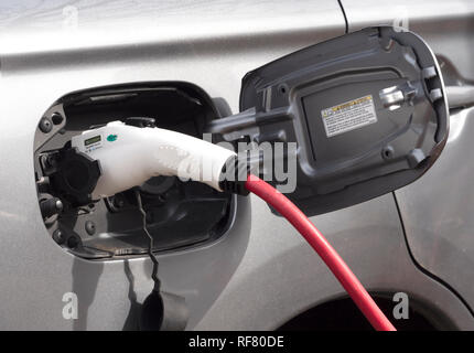 Close up of an electric car being charged. - Stock Photo