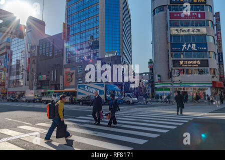Pedestrians crowded crossing at outside Ueno station in Tokyo Japan. Pedestrians walking and shopping at Ueno district on holiday. - Stock Photo