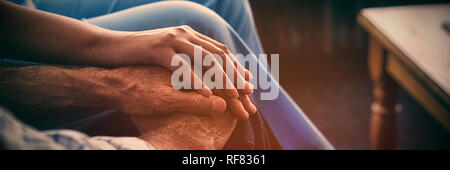 Cropped image of female doctor consoling senior man - Stock Photo