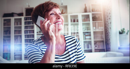 Senior woman talking on mobile phone in living room - Stock Photo