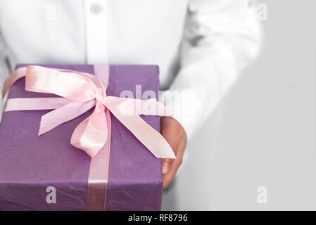 Child holding big purple present box wrapped on  pink ribbon in hands. Valentines day, mothers day or birthday celebration concept. Selective focus. C - Stock Photo