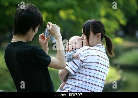 Couple with a baby, Yoyogi Park, Harajuku, Tokyo, Japan, Asia - Stock Photo