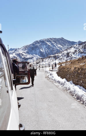 Traffic jam and Highway blockage due to snowfall at Tsomgo Lake. Tourist vehicles lined up to climb in step hill region of himalayan mountain valley. - Stock Photo