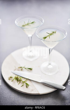 Summer drink. Refreshing summer alcoholic cocktail with rosemary or sparkling gin and lemonade on marble serving plate over dark concrete table. Copy