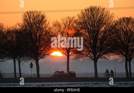 Sunset, motorists and cyclists on a country road in wintertime near Duisburg, North Rhine-Westphalia - Stock Photo
