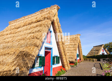 Palheiro house Santana Madeira Traditional triangular A-framed Palheiro Houses Santana Madeira Portugal red blue and white painted house portuguese - Stock Photo