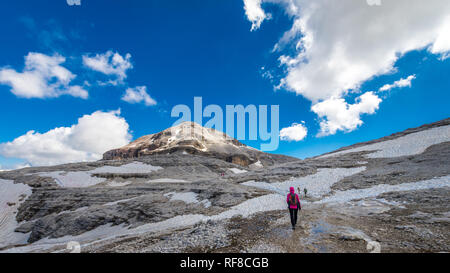 Tourists going to Piz Boe peak, 3152 m, in Sella massif, Dolomiti, Italy. View of rocky landscape from the hiking path. - Stock Photo