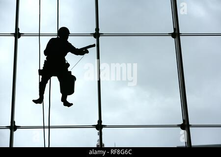 Window washer hanging against the glass facade of a skyscraper, Tokyo, Japan, Asia - Stock Photo