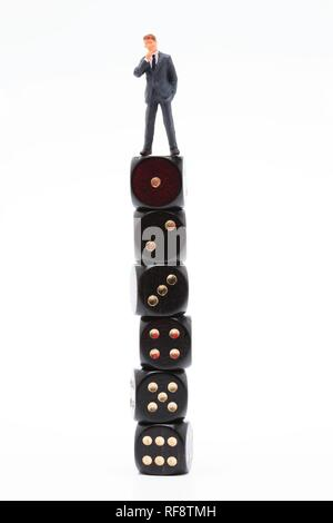 Small man standing on a large stack of dice: symbol for success - Stock Photo
