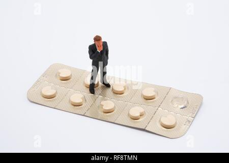 Small man standing on a large pill packet (beta blockers): symbol for skepticism of the pharmaceutical industry - Stock Photo