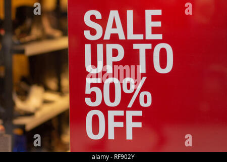 Red sign Sale up to 50 percentage off in shop window display - Stock Photo