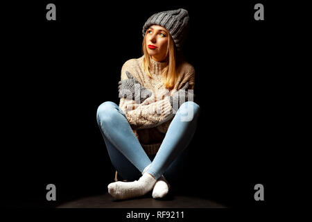 A blonde girl with make-up in a knitted brown sweater and hat with gloves is sitting off her legs crossed on the floor in the studio on a black backgr - Stock Photo