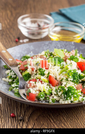 Salad with couscous, tomatoes, broccoli, tabbouleh, summer healthy dish - Stock Photo