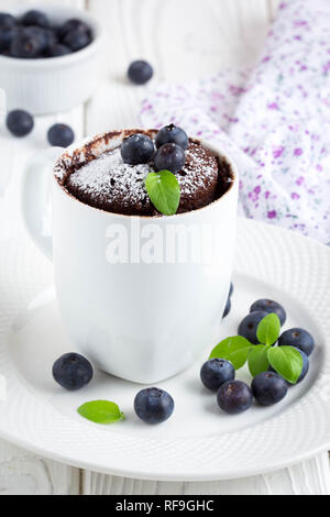 Chocolate cake in a mug with blueberry and powdered sugar, delicious summer dessert - Stock Photo