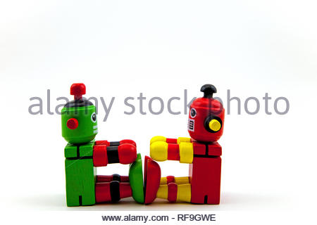 2 wooden toy robots, red/yellow & green/red, sitting facing each other with feet touching. Concepts exercising, communication. Copy space on white - Stock Photo