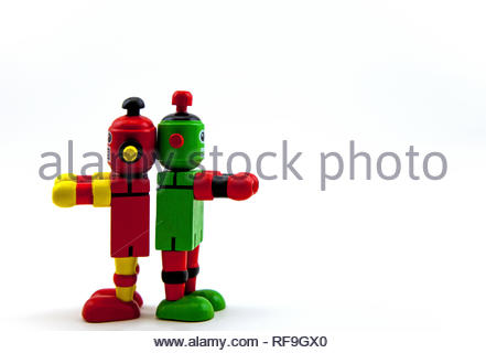 Two wooden toy robots, red/yellow & green/red, standing back to back and reaching out in front as if to walk away. Copy space on a white background - Stock Photo