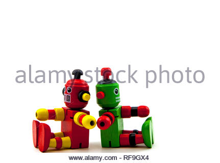 2 wooden toy robots, red & yellow and green & red, sitting back to back, but reaching out to touch each other. Copy space on a white background - Stock Photo