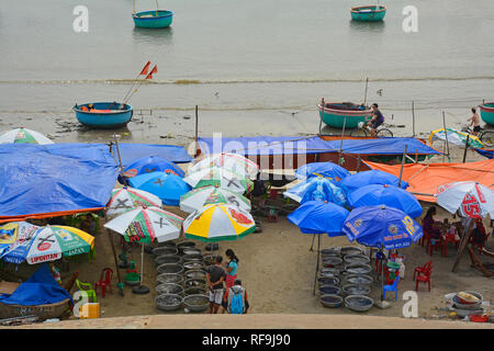 Mui Ne, Vietnam - December 27 2017. Customers eat at an outdoor restaurant and inspect the catch in Mui Ne Fishing Village - Stock Photo